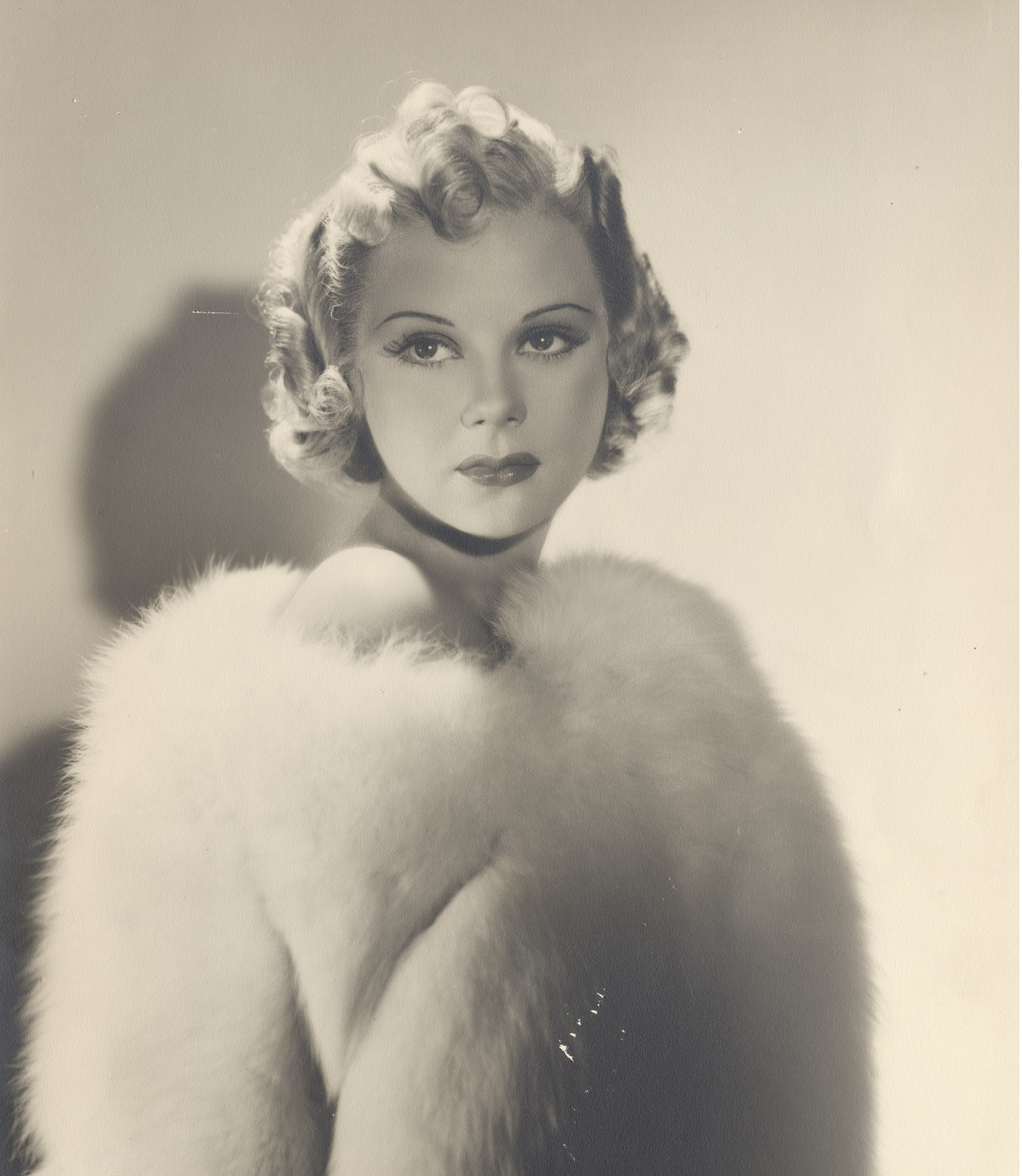 Movie star Sonja Henie posing in white fur